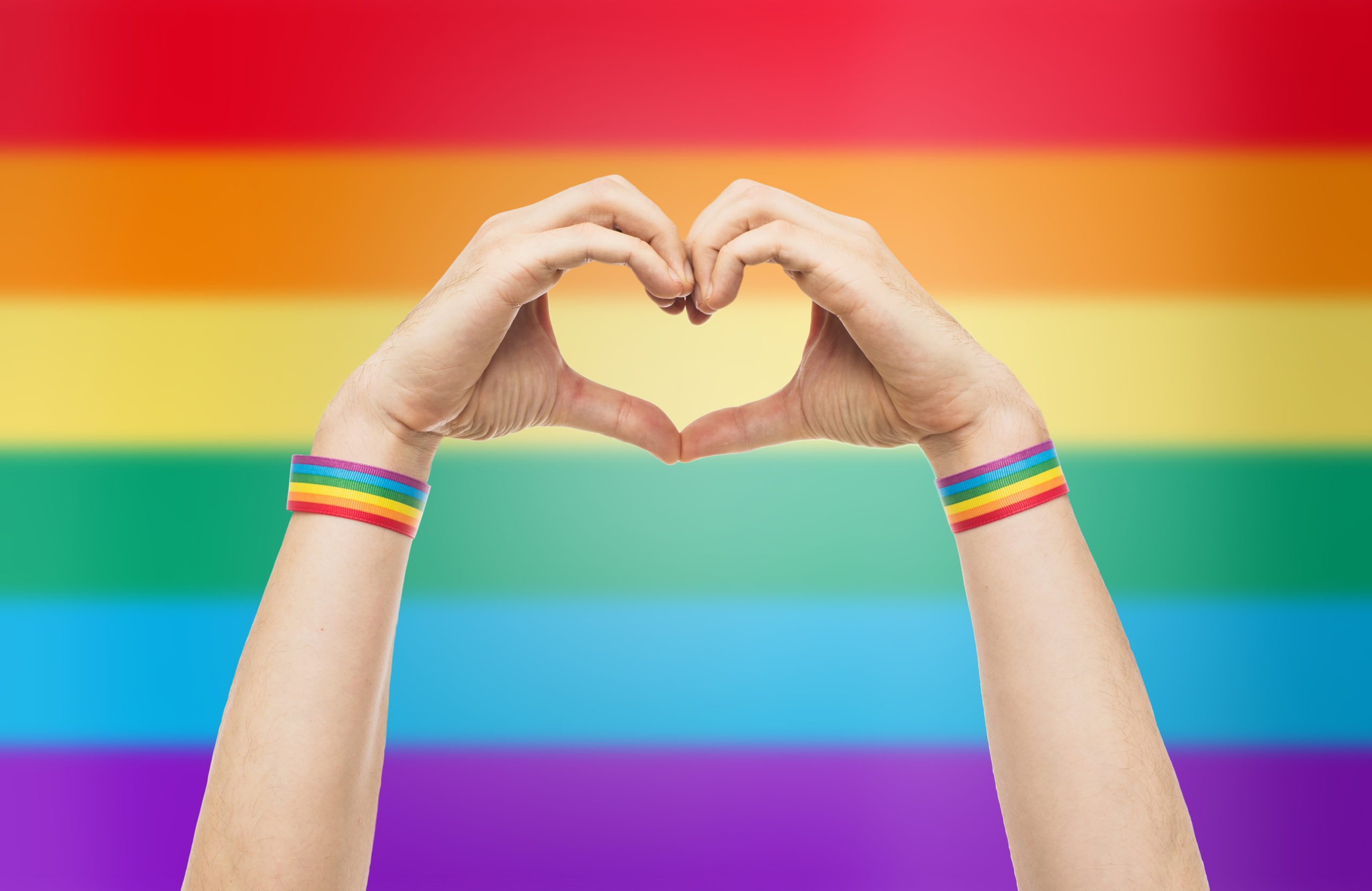 lgbt, same-sex love and homosexual relationships concept - close up of male hands with gay pride awareness wristbands showing heart gesture over rainbow background